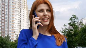 Una muchacha hermosa joven con los paseos rojos del pelo alrededor de la ciudad, contesta a la llamada de un teléfono móvil y es  metrajes