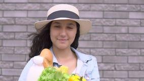 Una muchacha hermosa joven en una chaqueta y un sombrero del dril de algodón está sosteniendo un bolso de verduras, de la leche y almacen de video