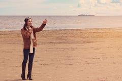 Una muchacha hermosa joven en la ropa del piloto abraza en la orilla de la bahía y ve apagado, o encuentra alguien con una ola el Imagen de archivo