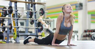 Una muchacha hermosa joven en un gimnasio, inclinándose en sus manos, sacude la prensa, haciendo los pasos largos, doblando sus r Fotografía de archivo libre de regalías
