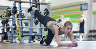 Una muchacha hermosa joven en un gimnasio, inclinándose en sus manos, sacude la prensa, haciendo los pasos largos, doblando sus r Imagenes de archivo