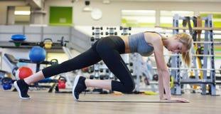 Una muchacha hermosa joven en un gimnasio, inclinándose en sus manos, sacude la prensa, haciendo los pasos largos, doblando sus r Imagen de archivo libre de regalías