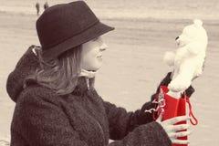 Una muchacha hermosa joven en un sombrero se sienta en la orilla de la bahía y es feliz de recibir un oso de peluche como present Imagenes de archivo