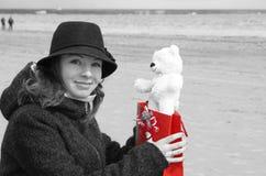 Una muchacha hermosa joven en un sombrero se sienta en la orilla de la bahía y es feliz de recibir un oso de peluche como present Imágenes de archivo libres de regalías