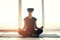 Una muchacha hermosa joven en vidrios de la realidad virtual hace yoga y aeróbicos remotamente Concepto futuro de la tecnología m Foto de archivo