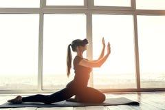 Una muchacha hermosa joven en vidrios de la realidad virtual hace yoga y aeróbicos remotamente Concepto futuro de la tecnología m Foto de archivo libre de regalías