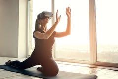 Una muchacha hermosa joven en vidrios de la realidad virtual hace yoga y aeróbicos remotamente Concepto futuro de la tecnología m Imagen de archivo libre de regalías