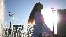 Una muchacha hermosa joven está haciendo girar cerca de una fuente en una ciudad en el verano HD, 1920x1080 Cámara lenta almacen de metraje de vídeo