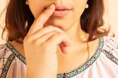 Una muchacha hermosa joven perceptible toca los labios Imagen de archivo libre de regalías