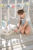 Una muchacha hermosa joven se sienta en la playa guarda los juguetes y sonrisa Foto de archivo