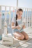 Una muchacha hermosa joven se sienta en la playa guarda los juguetes y sonrisa Imagenes de archivo