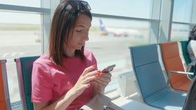 Una muchacha hermosa joven se sienta en la sala de espera del aeropuerto y utiliza un teléfono móvil E-boleto de la compra de la  metrajes