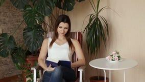 Una muchacha hermosa joven toma un libro de una tabla y comienza a leer Mujer que lee un libro que se sienta en una silla almacen de metraje de vídeo
