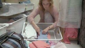 Una muchacha hermosa, una madre joven coge y dobla la ropa de los niños en cestas en su vestuario introduce cosas metrajes