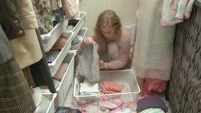 Una muchacha hermosa, una madre joven coge y dobla la ropa de los niños en cestas en su vestuario introduce cosas almacen de metraje de vídeo
