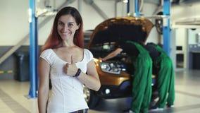 Una muchacha hermosa mira cómo dos mecánicos trabajan en el servicio del coche almacen de metraje de vídeo