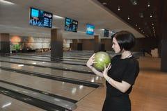Una muchacha hermosa mira el sketch y está a punto de hacer un tiro del globo de los bolos Juego del bowling Imagen de archivo