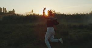 Una muchacha hermosa que baila alrededor mientras que el sol fija en el medow Cámara lenta metrajes