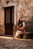 Una mujer linda que se sienta en un banco de piedra en un st mediterráneo viejo Fotografía de archivo