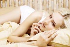 Una muchacha hermosa que se reclina sobre la cama Foto de archivo libre de regalías