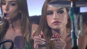 Una muchacha hermosa se sienta al lado de cachimbas y toca dibs del póker en sus manos metrajes