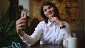 Una muchacha hermosa se sienta en un café y después de bebido un coffe caliente, presenta para que una cámara del teléfono móvil  almacen de metraje de vídeo