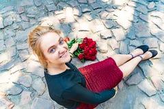 Una muchacha hermosa y atractiva se sienta en un camino del ladrillo, y un ramo de rosas rojas miente de lado a lado en el piso foto de archivo libre de regalías