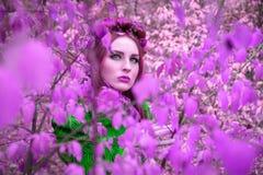 Una muchacha hermosa y fabulosa en un follaje rosado con la guirnalda roja Foto de archivo