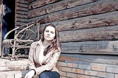 Una muchacha hermosa y una casa vieja Imagenes de archivo