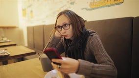 Una muchacha impaciente joven frustrada en vidrios falta el café La mujer cansada está esperando al novio y se agujerea metrajes