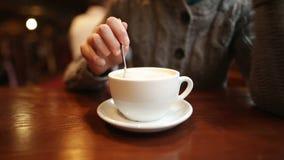 Una muchacha impaciente joven frustrada revuelve el azúcar en una taza blanca La mujer cansada está esperando al novio y la aburr metrajes