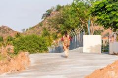 Una muchacha india con una mochila camina abajo de la calle Visión posterior Copie el espacio para el texto Fotografía de archivo