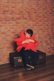 Una muchacha joven de la moda se sienta en la maleta en chaqueta de cuero roja con las estrellas rojas en sus manos Fotografía de archivo libre de regalías