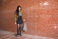Una muchacha joven del inconformista está montando un monopatín Novias f de las muchachas Fotos de archivo
