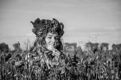 Una muchacha joven, feliz, hermosa se está divirtiendo y está bailando con alegría en el campo de amapolas florecientes con una g Fotos de archivo