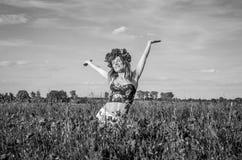 Una muchacha joven, feliz, hermosa se está divirtiendo y está bailando con alegría en el campo de amapolas florecientes con una g Imagen de archivo libre de regalías
