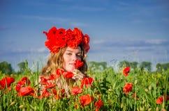 Una muchacha joven, feliz, hermosa se está divirtiendo y está bailando con alegría en el campo de amapolas florecientes con una g Fotos de archivo libres de regalías