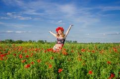Una muchacha joven, feliz, hermosa se está divirtiendo y está bailando con alegría en el campo de amapolas florecientes con una g Foto de archivo libre de regalías