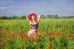 Una muchacha joven, feliz, hermosa se está divirtiendo y está bailando con alegría en el campo de amapolas florecientes con una g Imagenes de archivo