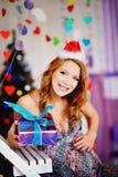 Una muchacha joven, hermosa en un casquillo del ` s del Año Nuevo, un dre futuro de la madre Foto de archivo libre de regalías