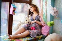 Una muchacha joven, hermosa, la mujer embarazada se sienta en una ventana s fotos de archivo libres de regalías