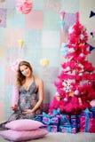 Una muchacha joven, hermosa, una madre futura vistió para arriba un árbol y un p foto de archivo