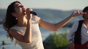 Una muchacha joven y bonita canta una canción enérgica en un micrófono al aire libre metrajes