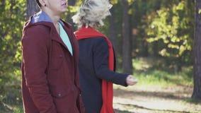 Una muchacha juguetona joven hermosa con el pelo rubio en una capa y una bufanda roja corre lejos de su novio en el bosque metrajes