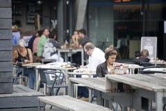 Una muchacha lee una revista, escucha la música y bebe la cerveza en un café imagenes de archivo