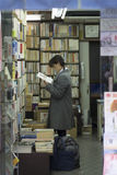 Una muchacha lee un libro en una librería Asakusa, Tokio, Japón fotografía de archivo