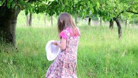 Una muchacha linda baila en el jardín natural La niña baila y salta en un pequeño trampolín La niña lleva floral almacen de video