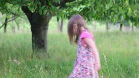 Una muchacha linda baila en el jardín natural La niña baila y salta en un pequeño trampolín La niña lleva floral metrajes