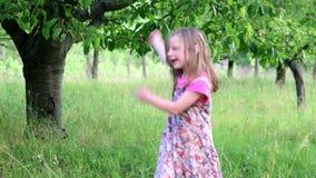 Una muchacha linda baila en el jardín natural La niña baila y salta en un pequeño trampolín La niña lleva floral almacen de metraje de vídeo