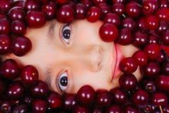 Una muchacha linda bajo muchos pedazos de cereza fotos de archivo libres de regalías